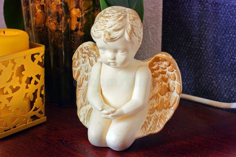 Figurilla del ángel en la mesita de noche El paisaje en la casa imagenes de archivo