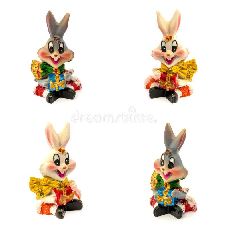 Figurillas de los conejos blancos y grises con los regalos aislados en un fondo blanco fotos de archivo libres de regalías