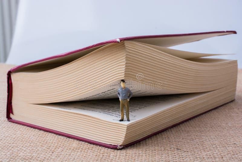 Figurina che sta dentro le pagine di un libro immagine stock libera da diritti