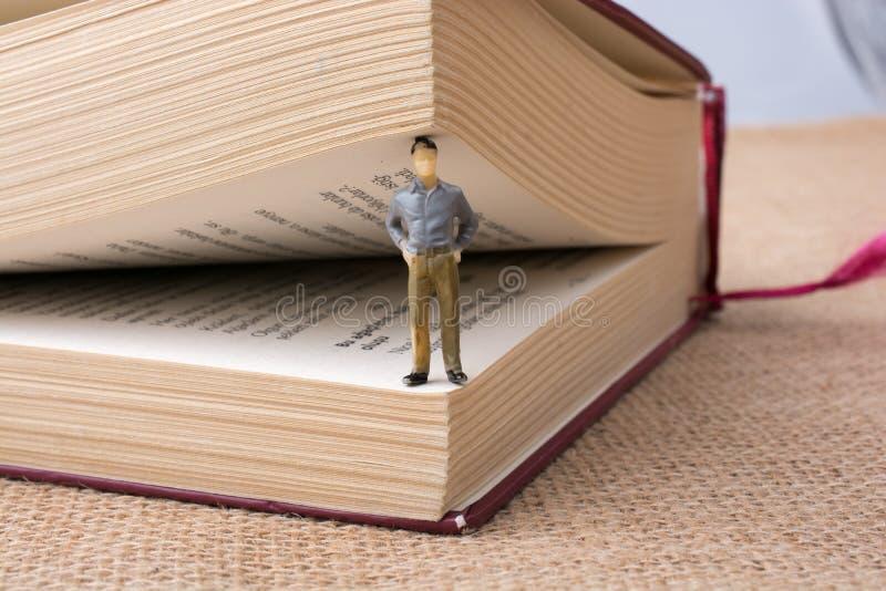 Figurina che sta dentro le pagine di un libro fotografie stock