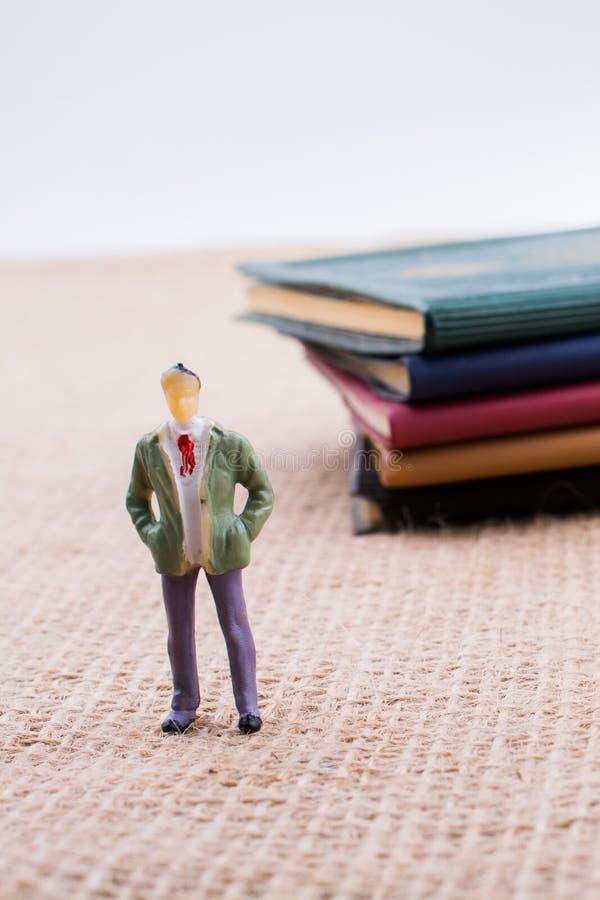Figurina che sta dentro le pagine di un libro fotografia stock