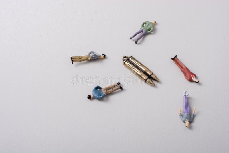 Figurina degli uomini intorno alla pallottola come concettuale contro la guerra immagine stock