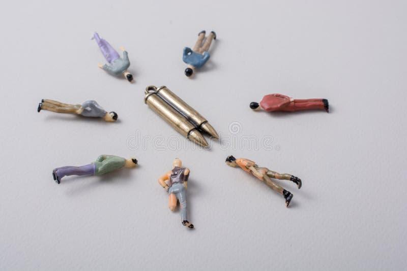 Figurina degli uomini intorno alla pallottola come concettuale contro la guerra fotografia stock
