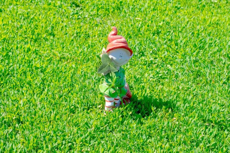 Figurina di Gnome con una foglia del trifoglio in sue mani fotografia stock