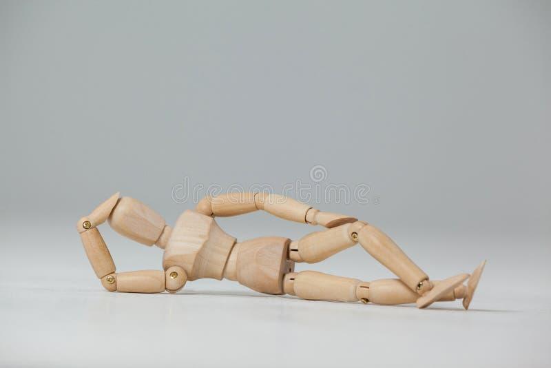 Figurina di legno che si adagia sul pavimento con la mano sulla testa immagini stock libere da diritti