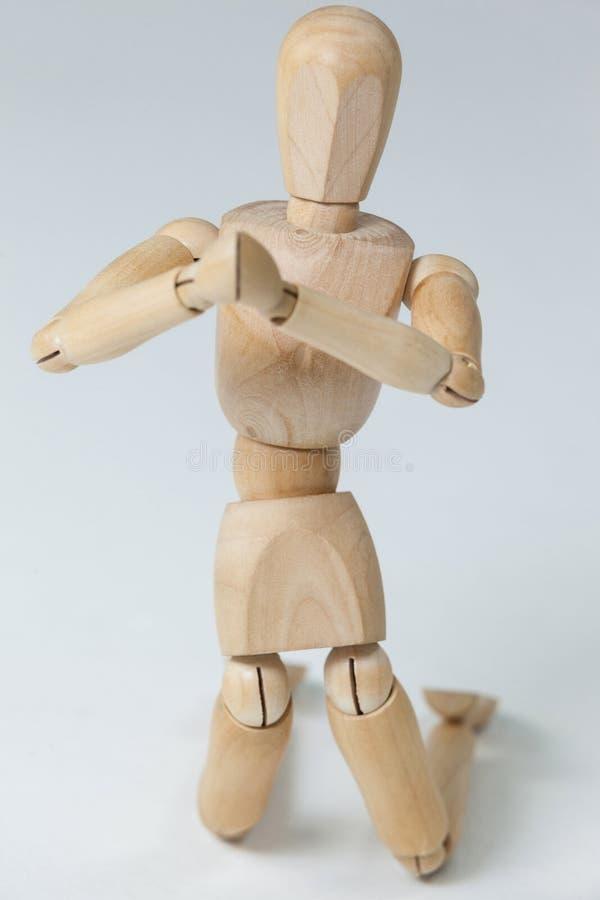 Figurina di legno che si inginocchia con entrambe le mani unite fotografie stock