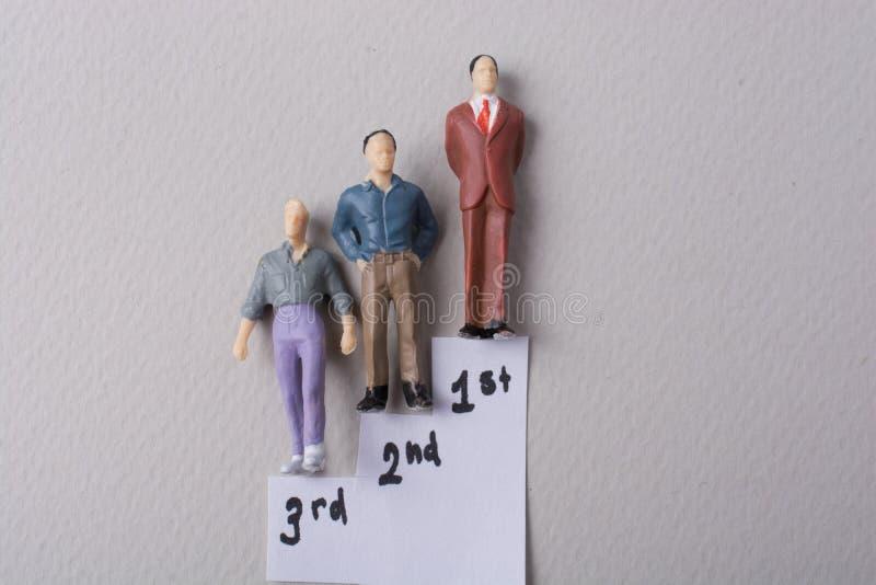 Figurina minuscola del modello dell'uomo nelle fasi fotografie stock libere da diritti