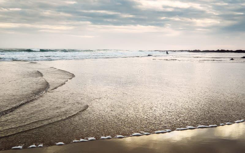 Figurina minuscola di Surfingman sulla spiaggia dell'oceano a tempo di alba fotografie stock