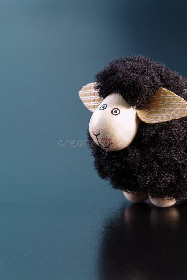 Figurina sorridente del giocattolo delle pecore nere con le grandi orecchie su una superficie blu fotografie stock libere da diritti