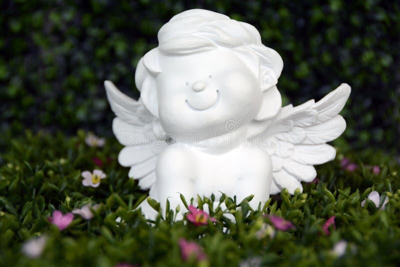 Белый Figurine Анджела керамический на зеленой траве с белым и фиолетовым цветком стоковые фото