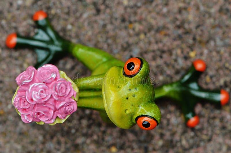 Лягушка держа пук Figurine цветка стоковое изображение rf