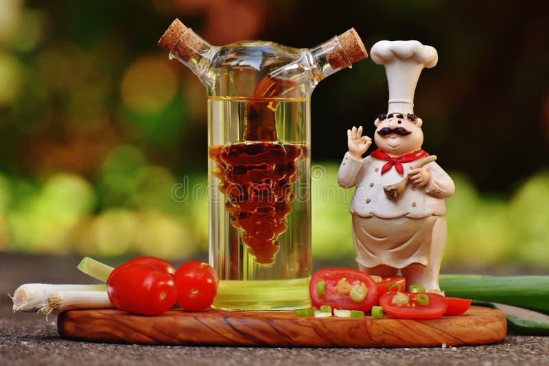 Figurine шеф-повара около ясных стеклянной бутылки и томатов стоковое изображение rf