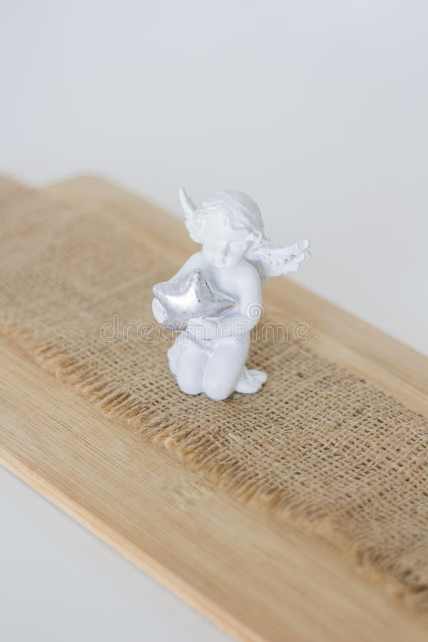 A figurine is an angel on wooden backgroun stock photography