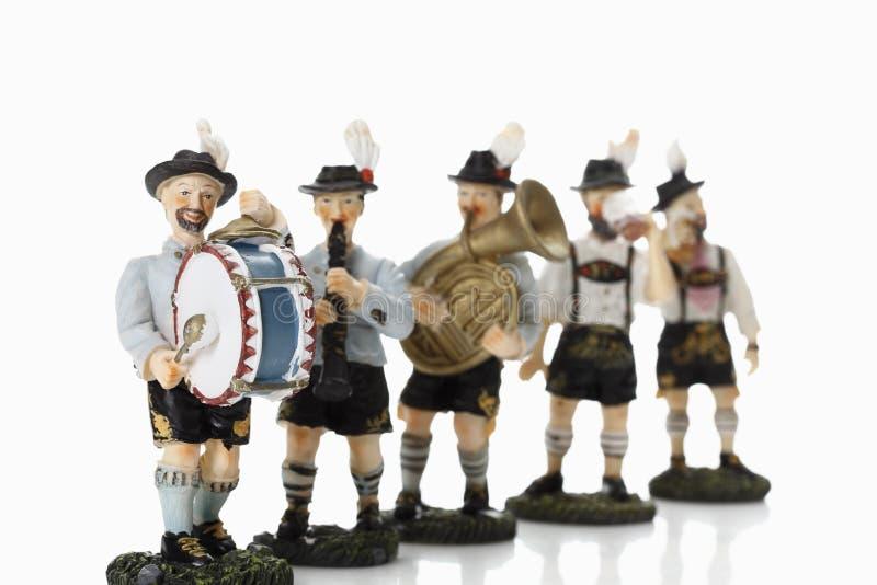 Figurine bavaresi che giocano musica su fondo bianco fotografia stock