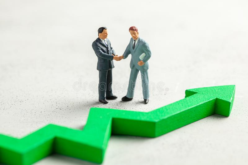Figurine of businessmen shaking hands in suit and tie and green up arrow. The concept of success, profit growth and an increase in royalty free stock image