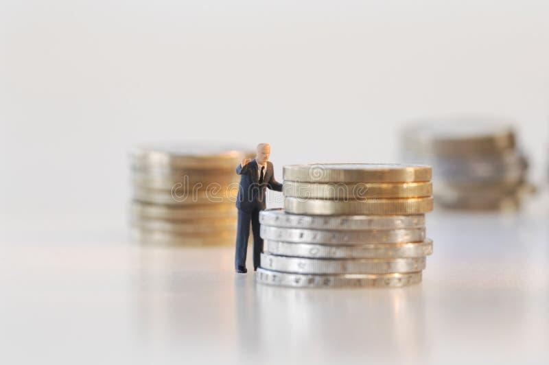 Figurine d'homme d'affaires prévoyant au sujet de la pension de retraite photos libres de droits