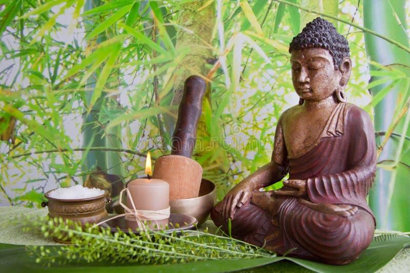 Figurine de Bouddha avec du sel de bain et une bougie photos stock