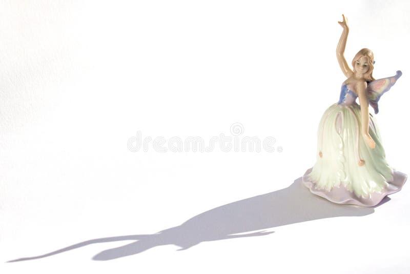 Figurine de porcelaine d'un danseur dans une robe avec les ailes et l'ombre photographie stock