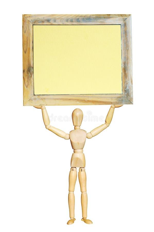 Figurine di legno che tiene una cornice fotografia stock libera da diritti