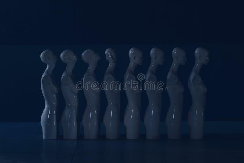 Figurine di plastica della donna che stanno nella linea in colata blu immagine stock libera da diritti