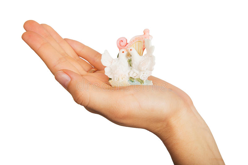 Figurine doves on a female hand. Isolated on white background royalty free stock images