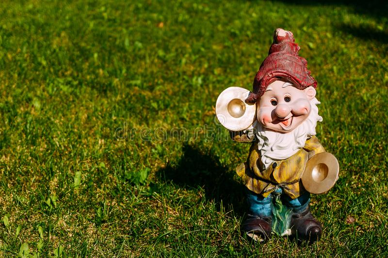 Figurine of a dwarf on the grass. Figurine of funny dwarf on the grass royalty free stock photos