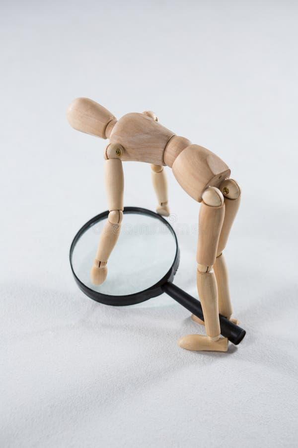 Figurine en bois prenant une loupe photo stock
