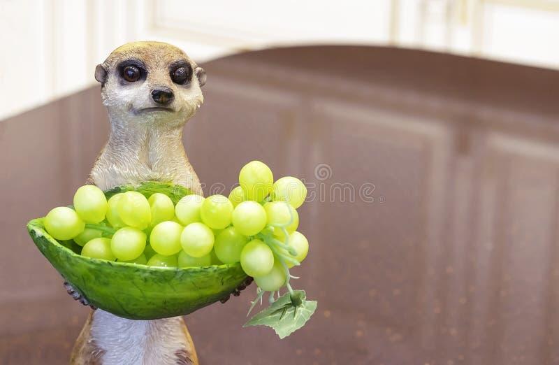 Figurine en céramique d'un meerkat avec un vase de raisins photographie stock