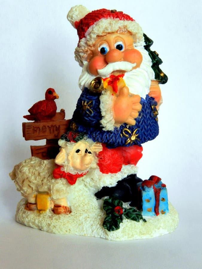 Figurine en céramique miniature de Santa Claus gaie d'isolement sur le fond blanc qui porte des cadeaux et souhaite tout le Joyeu images libres de droits