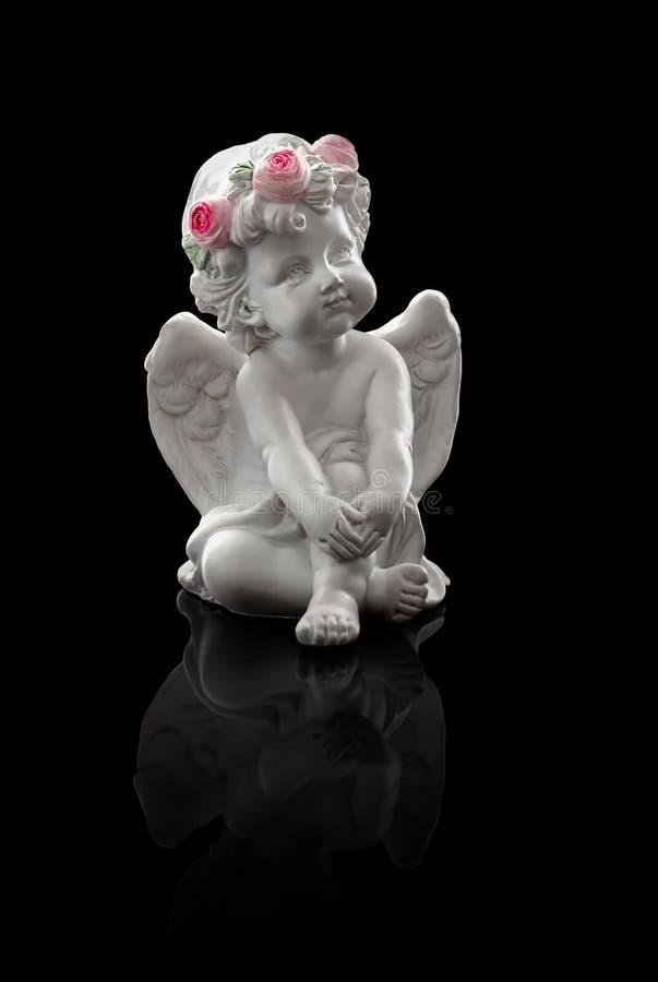 Figurine Fiporcelain усаженного ангела, с крыльями, черная предпосылка, отражение, день Валентайн стоковые фото