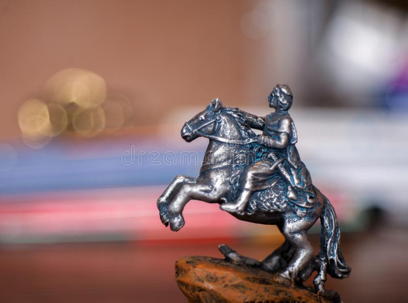 A figurine of a tin soldier on a horse with blurred background stock image