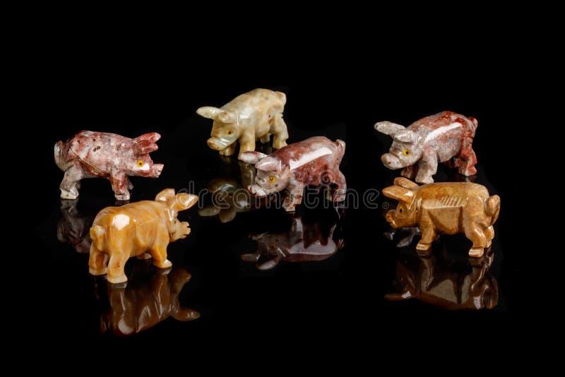 Figurines свиньи сделали из оникса, яшмы, стекла, золота на черной предпосылке стоковые фотографии rf