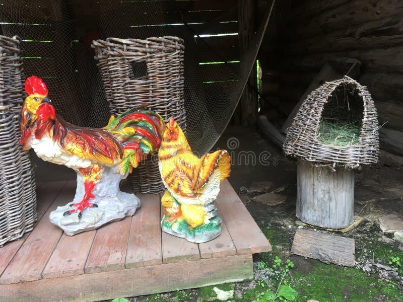 Figurines фарфора петухов стоя на улице около плетеных корзин стоковое изображение rf