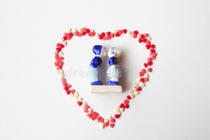 Figurines фарфора целовать мальчика и девушки в национальных голландских костюмах на белой предпосылке в середине сердца стоковые фотографии rf