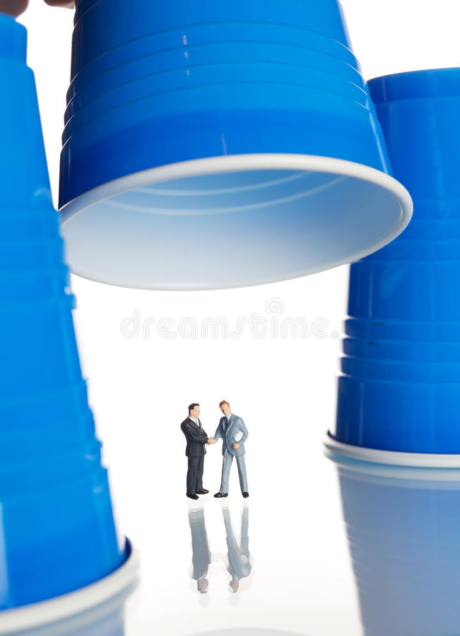 Figurines d'affaires sous les cuvettes de café en plastique image libre de droits