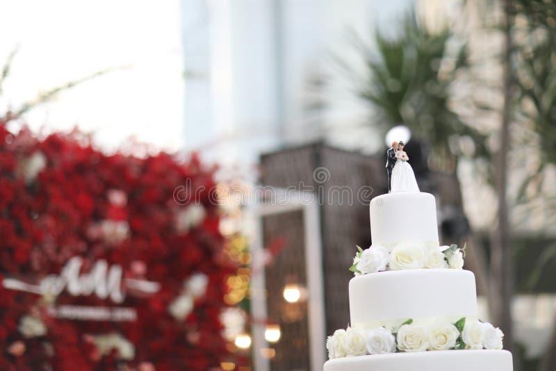 Figurines des jeunes mariés sur un gâteau de mariage Suite drôle de figurines à un gâteau blanc de mariage de luxe décoré photographie stock libre de droits