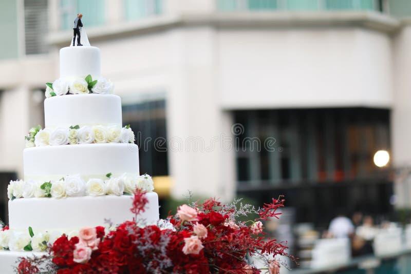 Figurines des jeunes mariés sur un gâteau de mariage Suite drôle de figurines à un gâteau blanc de mariage de luxe décoré photos libres de droits