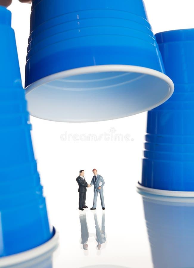 Figurines di affari sotto le tazze di caffè di plastica immagine stock libera da diritti