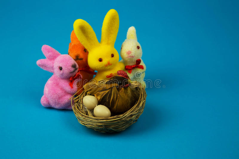 Figurines Easter bunnies and hen on a nest stock image