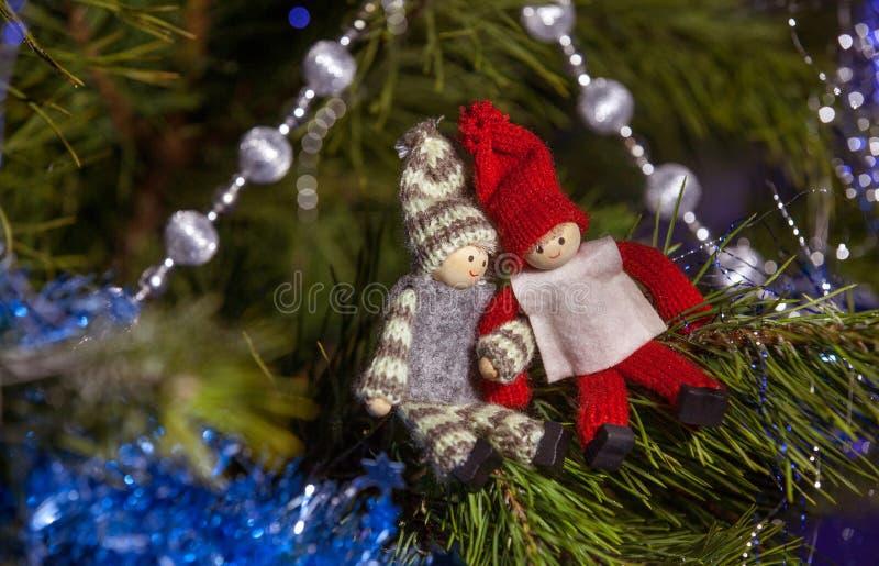 Figurines en bois de garçon et de fille sur la branche d'arbre de Noël Chri image libre de droits