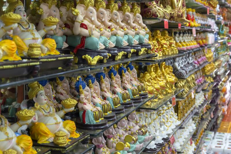 Figurines of Hindu and Buddhist gods for sale on the shelves of a religious store. In a temple stock photo
