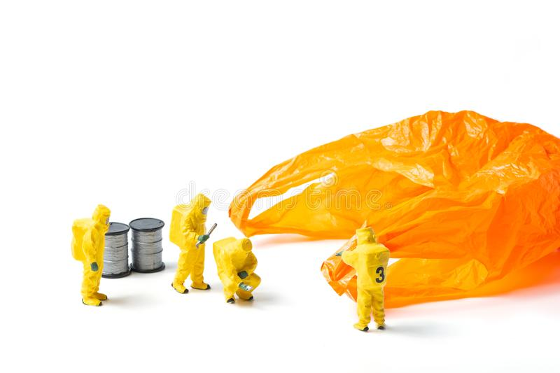 The figurines in protective suit examine an orange used plastic royalty free stock image