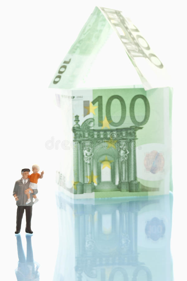 Figurines standing in front of house of 100 euro notes stock photography