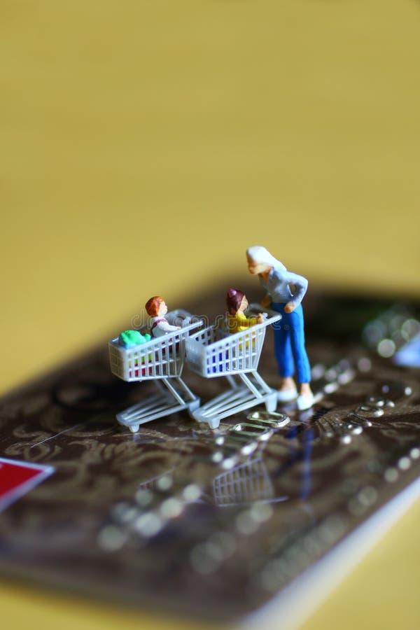 Figurines sur par la carte de crédit image stock