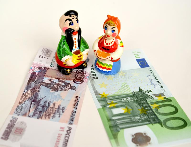 Figurines in the Ukrainian national suits stand on paper Russian and euro banknotes. Ukraine at the crossroads.  royalty free stock photos