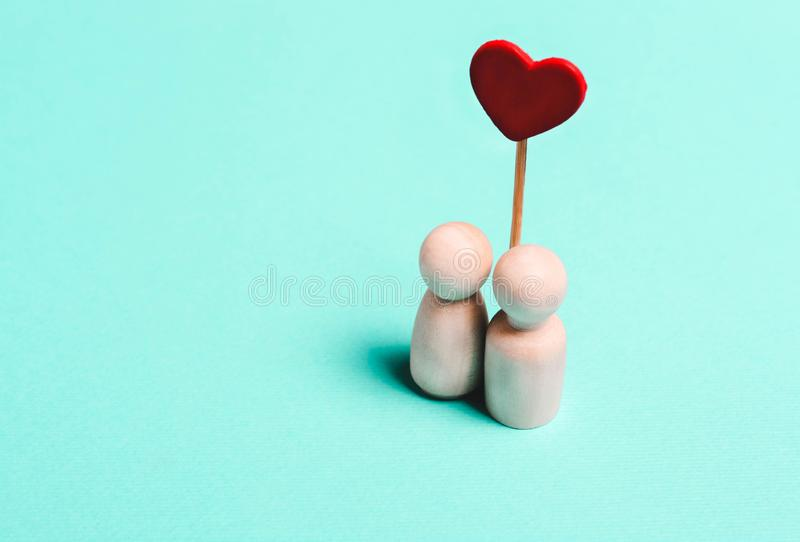 Figurines of a woman and a man with a heart on a blue background stock images