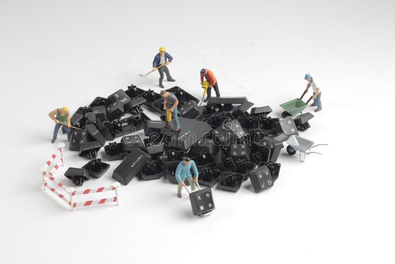 figurines of workers repairing computer key board stock images