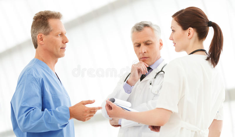Figuring out the correct medication. Three doctors discussing th. E report standing close to each other stock image