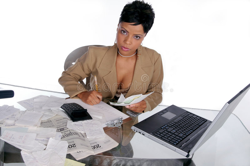 Figuring out her taxes. Young woman sits down to begin figuring out her taxes royalty free stock image
