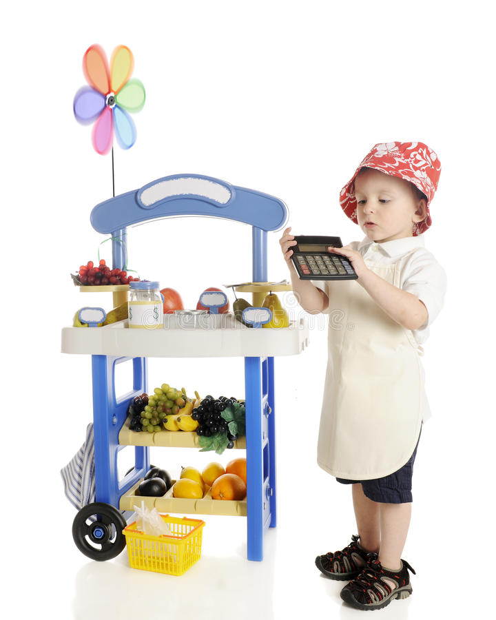 Figuring Vendor Profits. An adorable preschooler standing by his fruit stand while calculating his profits to show the viewer. The stand's signs are left blank stock image